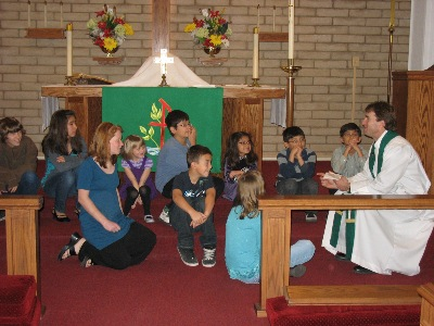 The Pastor gathers the children during worship for the Children's message